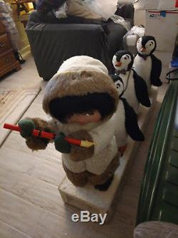 Harold Gale Eskimo playing flute with penguins following